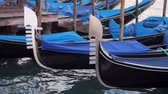 причал : Venetian Gondolas Close Up (HD). Blue gondola boats close up view docked near plaza Saint Marks Square in Venice Italy with far away view of San Giorgio Island.
