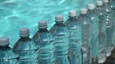 точка зрения : Water Bottles Row (HD). Row of generic unbranded water bottles with ripple water background. Стоковые видеозаписи