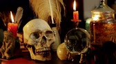 koponya : Skull Witchcraft Desk Artifacts (HD). Occult study setup desk with a skull chandelier, candles, crystal ball, books, and other occult paraphernalia. Skull is resin replica not real. Stock mozgókép