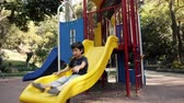 игривый : Kid Climbs and Slides on Playground Slide in Public Park.