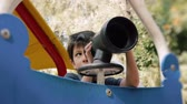 olhar : Hispanic Boy Playing with Toy Spyglass at Public Park.