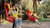 игривый : Mom Swinging Hispanic Kids on Swings at Public Park with Both Hands. Angle Five Стоковые видеозаписи