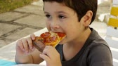 italiano : Kid with Acne Eats Pizza (HD). Six year old Hispanic boy eating a slice of pepperoni pizza with some acne on his face.
