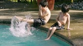 игривый : Brothers Splashing in Pool (HD). Two brothers of Hispanic origin; six and four years old splashing in swimming pool sprayed with water.