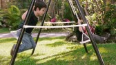 игривый : Kids playing on swing Side View (HD). Two brothers of hispanic origin; six and four years old playing on a swing set. Seen from the side.