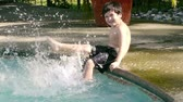 yüzme havuzu : Boy Splashing Pool Slow Motion (HD). Boy of hispanic origin; six years old splashing in pool with his legs as hard as he can. slow motion.