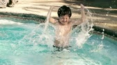 yüzme havuzu : Kid Tantrum in Water Slow Motion (HD). Kid splashing with arms in shallow pool water; Hispanic origin; six years old. Slow motion  Stok Video