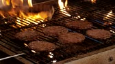 cooks : Close Up of Flipping Burgers In Metal Grill With Flames Shot in 4k