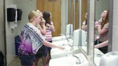 уборная : A few girls (students) putting on makeup while talking in a school restroom