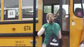High school kids getting on a school bus Wideo