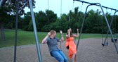 heterossexual : Young couple, in love, sitting on swings in a park playground together on a late summer (early fall) day. 4K