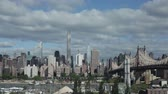 Midtown Manhattan skyline with East River and the Queensboro Bridge during cloudy spring day in New York City, USA.
