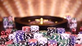 roleta : Poker Chips on gaming table, roulette wheel in motion