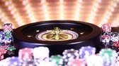 wijnen : Poker Chips on gaming table, roulette wheel in motion