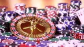 risque : Poker Chips on gaming table, roulette wheel in motion