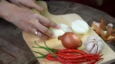 chalota : video footage hand slicing onion at cutting board