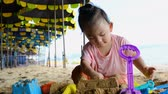 balde : Cute asian baby girl playing with beach toys on the beach