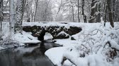 vento : Old Stone bridge covered with snow and small river flowing underneath with snow falling from the trees to the river