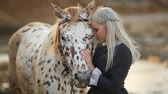 amazona : Young Blonde woman stroking and hugging horse. Beautiful lady with her white stallion on the seashore enjoying nature. Love and friendship concept. Waves ocean background.