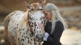 amazona : Young Blonde woman stroking and hugging horse. Beautiful lady with her white stallion on the seashore enjoying nature. Love and friendship concept. Waves ocean background