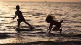 サーフボード : Happy children playing on the beach at the sunset time. Concept of summer vacation, friendly family