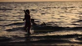 búfalo : silhouettes of children bathe in the golden sunset in the summer holidays at sea