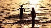 hassaslık : children walking by the sea at the sunset time Stok Video