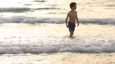 sıçramalarına : happy little boy run play with waves on beach