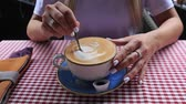 porcelana : Girl stirs coffee with a spoon, dripping drops, close-up, slow motion.