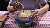 female hands with a spoon stirs sugar in coffee