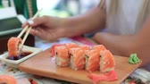 soja : Woman Hand With Chopsticks Dipping Sushi Roll into Soy Sauce