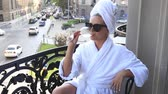 young woman in a bathrobe drinks champagne on the balcony 動画素材