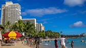 Tourists sunbathing and surfing on Waikiki beach in Oahu. Waikiki beach is beachfront neighborhood of Honolulu, best known for white sand and surfing