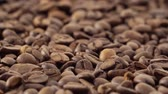 Close up video of panning over roasted coffee beans that are moving to the right in a circle