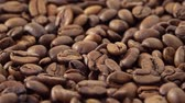 Close up video of panning over roasted coffee beans in a forward movement
