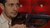 style : A young man plays the violin on a red background