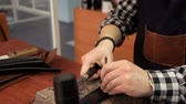 segregatory : The master makes holes in the leather belt. Leather belt manufacturing
