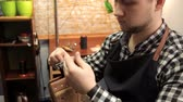 мятый : The master fastens the buckle on the leather belt, sews a needle. Procedure for the manufacture of leather belts