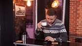 charismatic : Charismatic young man drinks coffee and uses a smartphone in a restaurant