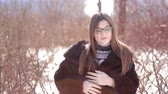 elegáns : Cute girl with glasses and mink fur coat and straightening hair outside in winter
