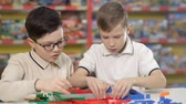 aviador : Two boys erect buildings from a childrens plastic designer Stock Footage