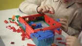 cúbico : Two children, developing, build from the plastic constructor of the building
