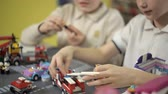 aviateur : In the toy store, two boys are building structures from cubes of a plastic designer