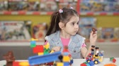 kreş : Cute little girl is playing with objects made of plastic elements, blocks of childrens designers