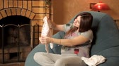 těhotná : Happy pregnant girl sits in an armchair by the fireplace and looks at clothes for newborns Dostupné videozáznamy