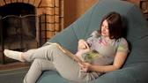elite : Happy pregnant girl sits in a chair by the fireplace and reads a book, stroking her belly
