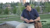 grosseiro : Middle-aged man is resting in a recreation park and looks at a fitness bracelet how many steps he has taken