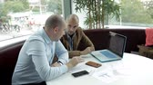дебаты : Two business men sit at a laptop and monitor the development of business. Business