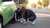 резервный : Girls the side of the road learn to change the tyre on his car