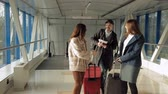 roll on bag : two girls and a guy meet at the airport before boarding the plane Stock Footage